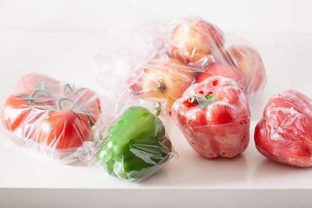 Einweg-kunststoffverpackungsproblem. paprika tomaten äpfel gemüse in plastiktüten