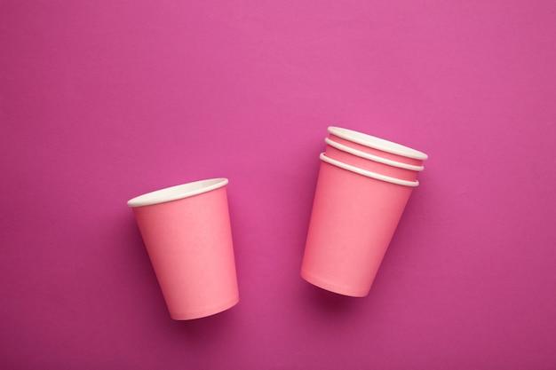 Einweg-pappbecher auf rosa hintergrund. ansicht von oben.
