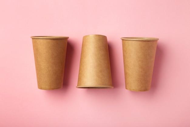 Einweg-pappbecher auf rosa hintergrund. kaffee-konzept.