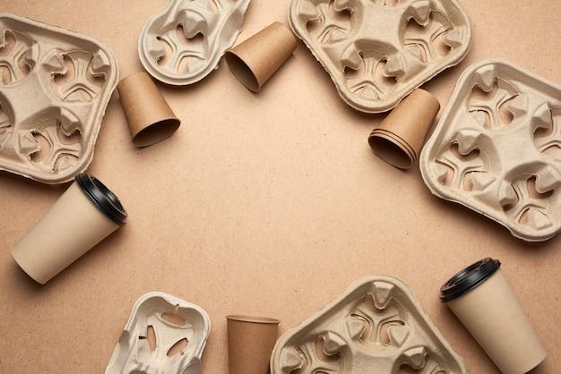 Einweg-pappbecher aus braunem bastelpapier und recyclingpapierhaltern auf braunem holzhintergrund