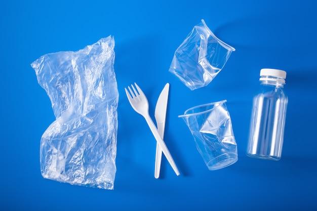 Einweg-plastikbecher, gabeln, löffel. konzept des recyclings von kunststoff, kunststoffabfällen