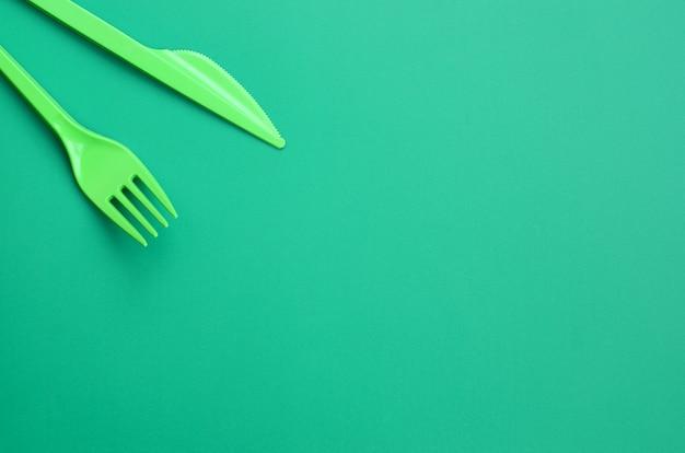 Einweg-plastikbesteck grün. plastikgabel und messer liegen auf einer grünen hintergrundoberfläche