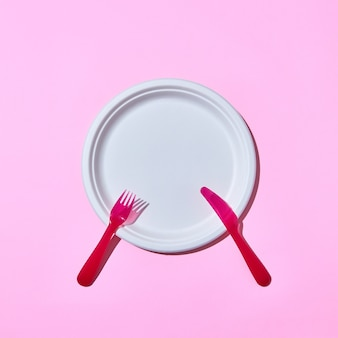 Einweg-plastikbesteck-set serviert gabel und messer auf einem rosa hintergrund mit kopienraum.