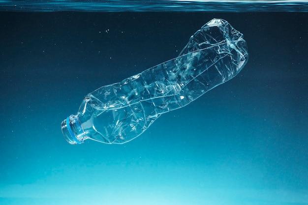 Einweg-plastikflasche, die im ozean schwimmt