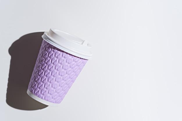 Einwegbecher aus lila papier auf weißem hintergrund mit schatten, verspotten