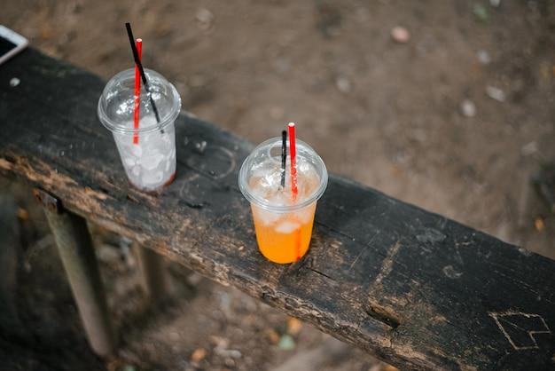 Einwegbecher mit frischem saft und eis auf der bank. erfrischendes kaltes getränk im heißen sommer.