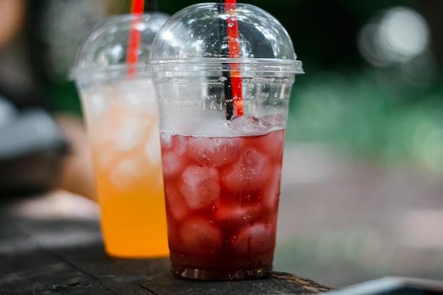Einwegbecher mit frischem saft und eis. erfrischendes kaltes getränk im heißen sommer.