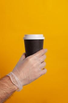 Einwegbecher von einer hand mit schutzhandschuh gehalten