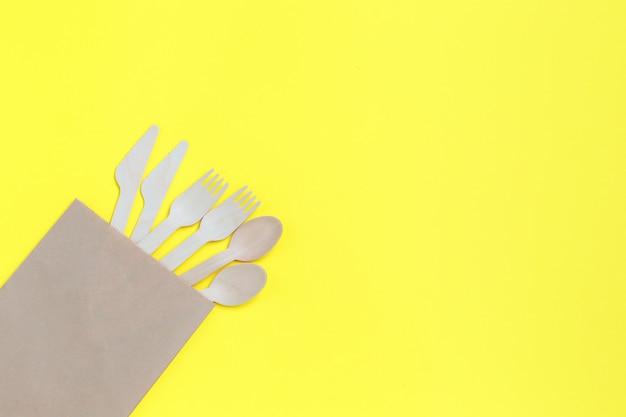 Einweggeschirr aus natürlichen materialien, holzlöffel, messer und gabeln in papiertüte auf gelb