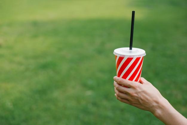 Einwegglas aus papier mit einem strohroten und weißen streifen für getränke in den händen einer frau