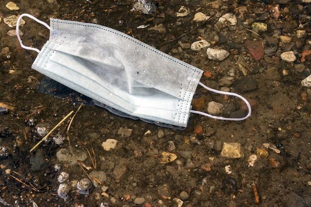 Einwegmaske liegt auf dem hintergrund des bodens. konzept des tages der erde zur reinigung des planeten von abfall.