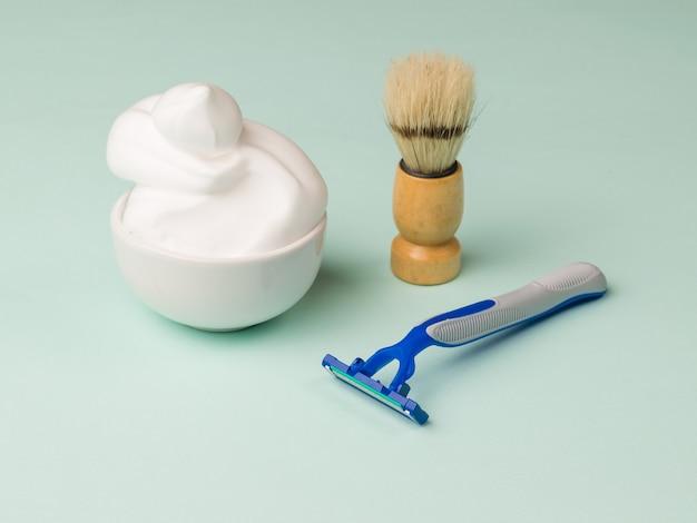 Einwegrasierer aus kunststoff, schaumstoff und ein rasierpinsel zum rasieren. stellen sie für die pflege des gesichts eines mannes ein.
