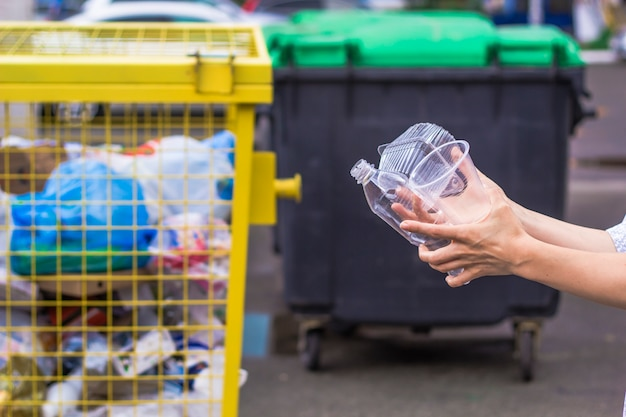 Einwegverpackung aus kunststoff in den händen in der nähe des müllcontainers.