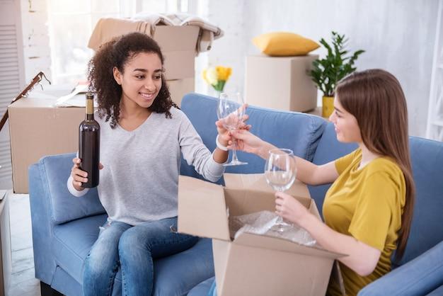Einweihungsparty. glückliche junge mädchen sitzen auf dem sofa und packen zwei weingläser aus, um den umzug in eine neue wohnung zu feiern