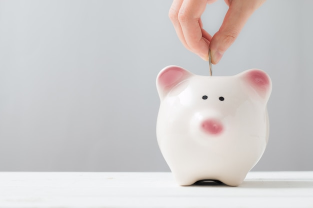 Einwurf einer münze in ein sparschwein. minimaler stil. geld sparen konzept.