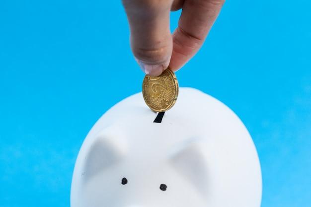 Einwurf einer münze in ein sparschwein