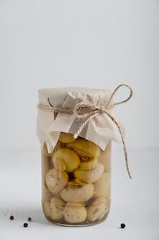 Einzelglas mit hausgemachten marinierten champignonpilzen auf weißem holztisch