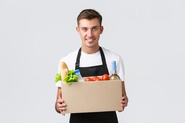 Einzelhandel mit lebensmitteleinkauf und lieferkonzept hübscher kurier in schwarzer schürze, der box mit g...