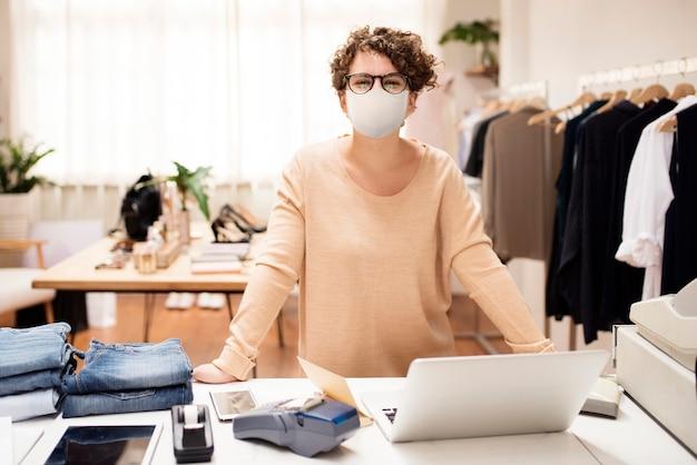 Einzelhandelsgeschäftsinhaber in der maske soziales distanzierendes einkaufen