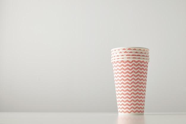 Einzelhandelsset von vier pappbechern verziert mit rotem linienmuster lokalisiert auf weißem tisch
