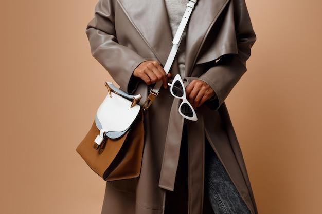 Einzelheiten. schwarze frau, die grauen ledermantel trägt und auf beigem hintergrund aufwirft. braune tasche und weiße sonnenbrille in den händen. herbst- oder wintermodekonzept.
