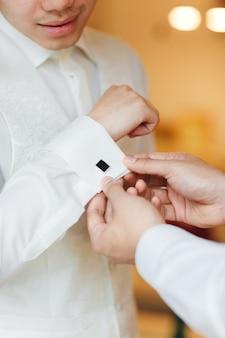 Einzelheiten. vorbereitungen für die hochzeit. hochzeit morgen bräutigam. vorbereitung des bräutigams am morgen, hübscher bräutigam, der sich anzieht und sich auf die hochzeit vorbereitet. groomsmen helfen dem glücklichen bräutigam, sich fertig zu machen