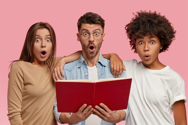 Einzelne aufnahme von verblüfften drei interracial freunden bereiten sich gemeinsam auf die abschlussprüfung vor