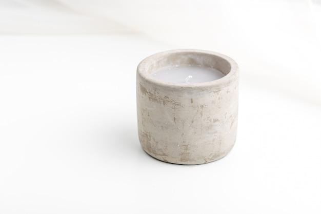 Einzelne betonkerze mit ätherischen ölen. minimalismus-konzept.