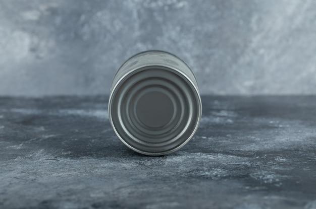 Einzelne blechdose auf marmor gestellt.