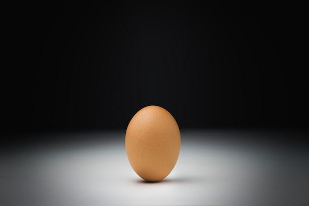Einzelne braune hühnerei auf weißer tabelle mit schwarzem hintergrund.
