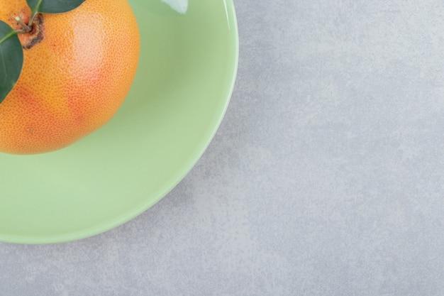 Einzelne frische clementine auf grünem teller.
