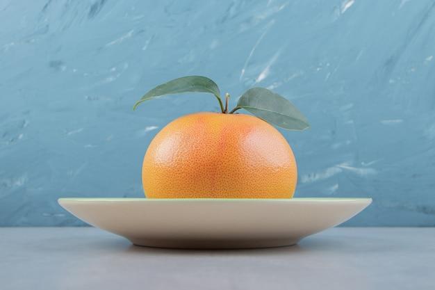 Einzelne frische clementine auf grünem teller