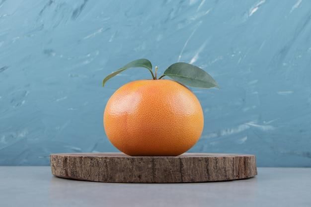 Einzelne frische clementine auf holzstück.