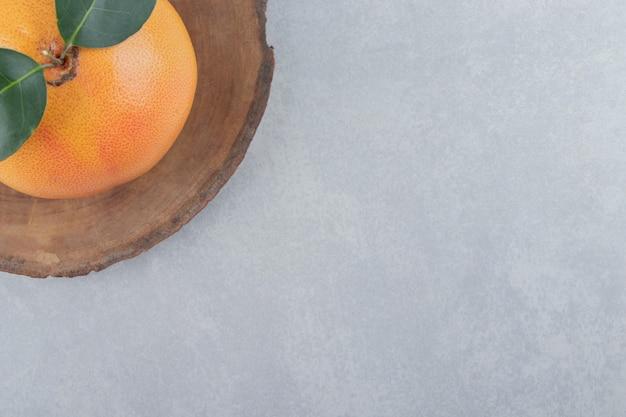 Einzelne frische clementine auf holzstück