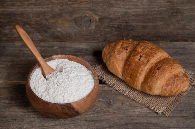Einzelne frische einfache croissant und schüssel mehl holzoberfläche. hochwertiges foto