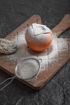 Einzelne frische kakifrucht mit mehl auf holzbrett
