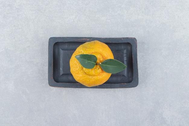 Einzelne frische mandarine mit blättern auf schwarzem teller.