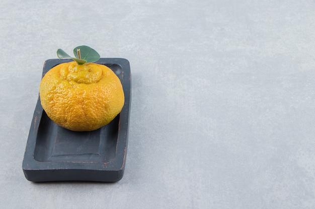 Einzelne frische mandarine mit blättern auf schwarzem teller