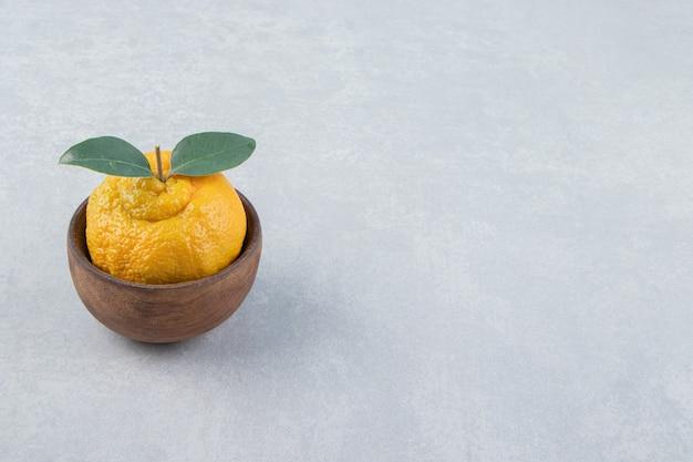 Einzelne frische mandarine mit blättern in holzschale
