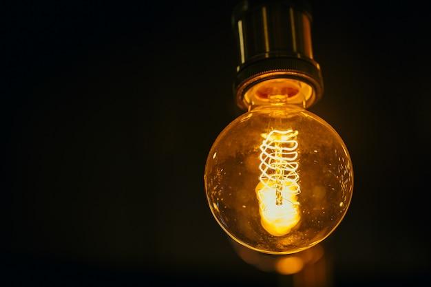 Einzelne glühlampe auf dunklem hintergrund mit platz für text.