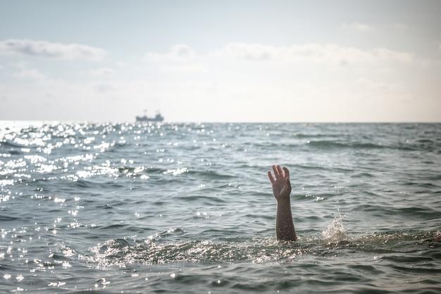 Einzelne hand des ertrinkenden im meer, der um hilfe bittet. aus dem wasser ragen