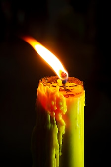 Einzelne helle flammenkerze oder bienenwachskerze, die hell auf schwarzem hintergrund brennt.