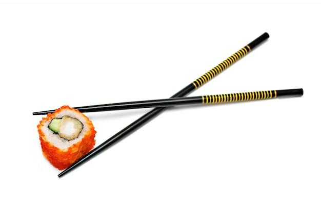 Einzelne japanische sushi-rolle in den stäbchen