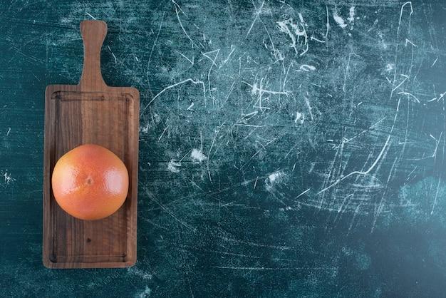 Einzelne leckere orange auf holzbrett.