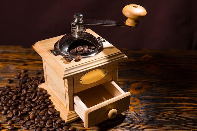 Einzelne manuelle kaffeemühle mit verstreuten bohnen