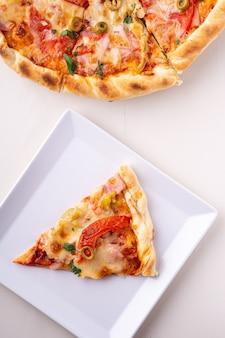 Einzelne pizzascheibe auf draufsicht der weißen platte und der ganzen pizza