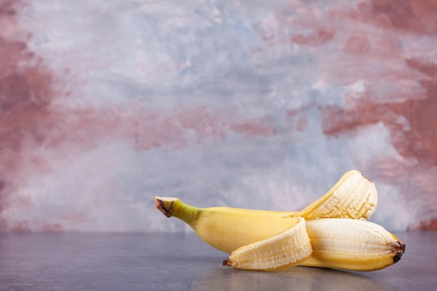 Einzelne reife gelbe banane, die auf steinhintergrund gelegt wird.
