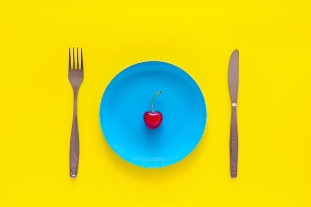 Einzelne reife kirsche auf blauer platte, messer, gabel auf gelbem hintergrund