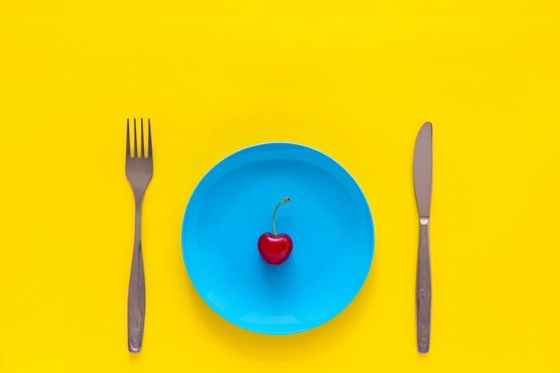 Einzelne reife kirsche auf blauer platte, messer, gabel. stillleben auf gelbem grund, draufsicht,