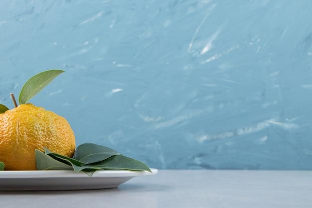 Einzelne reife mandarine mit blättern auf weißem teller.